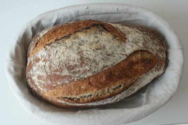 o pâine făcută din maia pusă într-un coș, pe o pânză albă.